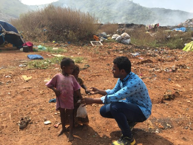 KISES worker Riyaz talks to two dump-dwelling children, while the fumes of burning rubbish fill the air